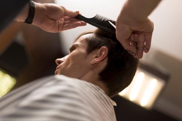 Schließen sie herauf den mann der niedrigen ansicht, der einen haarschnitt erhält