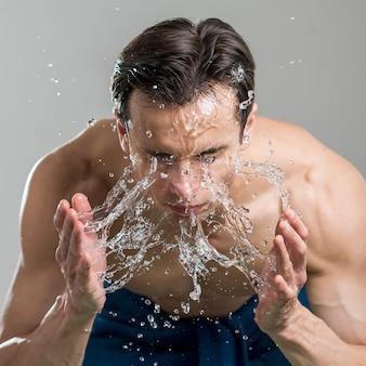 Schließen sie herauf den mann, der sein gesicht mit wasser wäscht