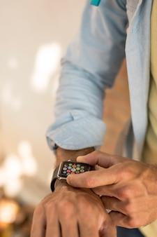 Schließen sie herauf den mann, der smartwatch überprüft