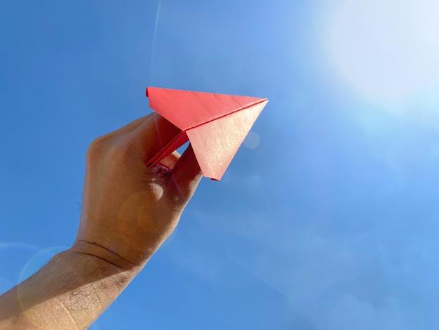Schließen sie herauf den menschen, der rotes papierflugzeug hält