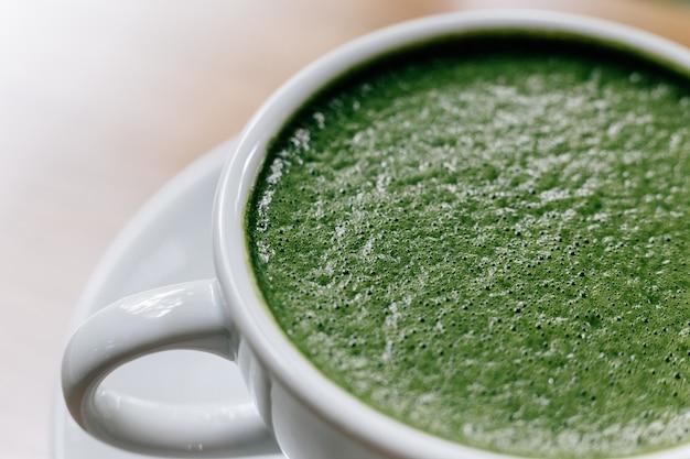 Schließen sie herauf den schaum des heißen und glatten latte grünen tees, der in der weißen keramischen schale gedient wird.