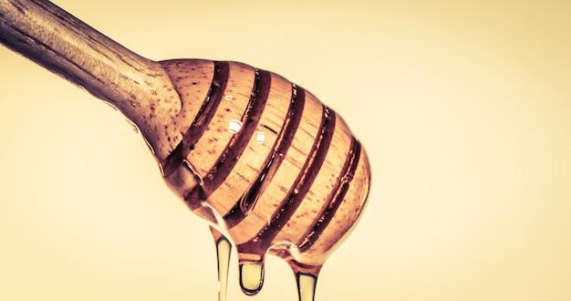 Schließen sie herauf den strömenden goldenen süßen honig, der auf honigschöpflöffel tropft