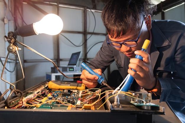 Schließen sie herauf den techniker, der leiterplatte mit solderer vorbereitet.