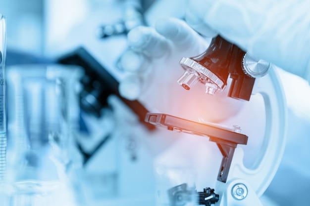 Schließen sie herauf den wissenschaftler, der mikroskop im laborraum bei der herstellung der medizinischen prüfung und der forschung verwendet