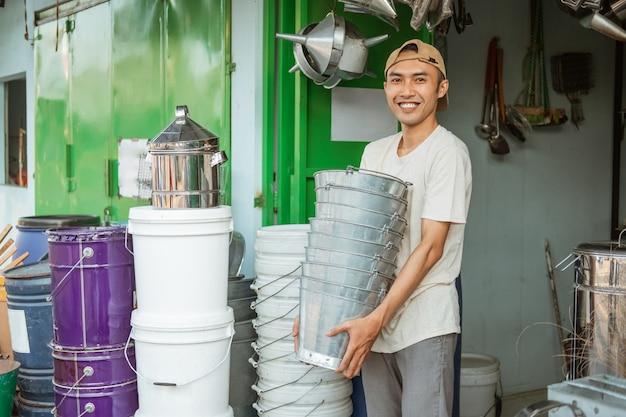 Schließen sie herauf des asiatischen männlichen lächelns, während sie viele eimer im haushaltsgerätespeicher tragen