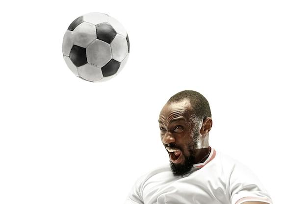 Schließen sie herauf des emotionalen afrikanischen mannes, der fußball spielt, der den ball mit dem kopf auf der isolierten weißen wand schlägt. fußball, sport, gesichtsausdruck, menschliche emotionen, gesundes lebensstilkonzept. copyspace.