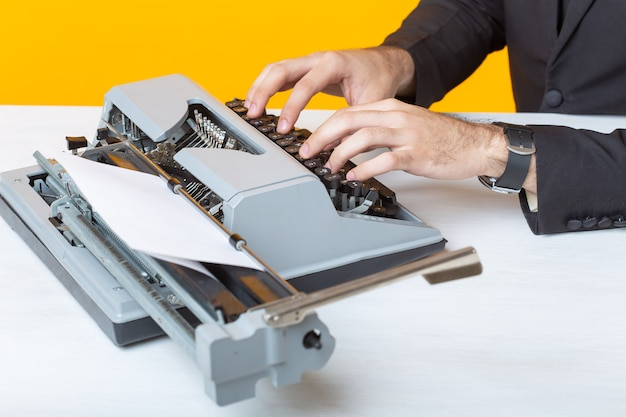 Schließen sie herauf des geschäftsmanns oder des managers im formellen anzug, der text auf einer schreibmaschine auf einer gelben oberfläche schreibt