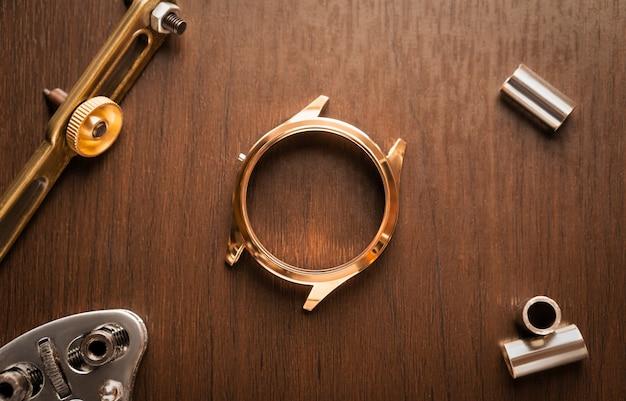 Schließen sie herauf des glänzenden goldenen edelstahl-uhrengehäuses, das auf reparatur wartet, weinleseholz-uhrmachertisch mit werkzeug und ausrüstung für service-hintergrundkonzept