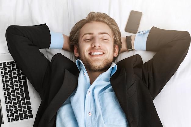 Schließen sie herauf des glücklichen fröhlichen bärtigen mannes im schwarzen anzug, der auf dem rücken mit laptop-computer und handy nahe ihm mit entspanntem ausdruck liegt, nachdem sie alle aufgaben erledigt haben.