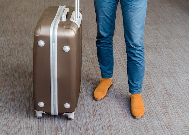 Schließen sie herauf des jungen geschäftsmannes mit koffergepäck auf dem teppich an der flughafenhalle