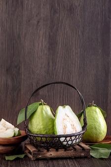 Schließen sie herauf des köstlichen schönen guavensatzes mit frischen grünen blättern lokalisiert auf holztisch