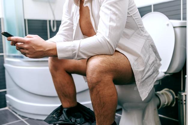 Schließen sie herauf des nicht erkennbaren geschäftsmannes, der smartphone zum schreiben oder lesen der nachricht verwendet, während sie auf der toilette sitzen.