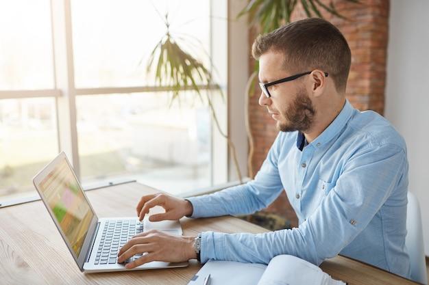 Schließen sie herauf des reifen ernsthaften bärtigen kaukasischen männlichen firmenleiters, der im großen bequemen büro sitzt, durch kundenliste auf laptop-computer schaut, notiz im notizbuch macht, produktive morgen verbringt