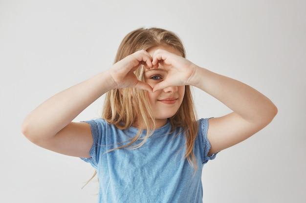 Schließen sie herauf des schönen blonden mädchens, das herz mit den händen macht, durch sie schaut und für foto mit lächeln und glücklichem ausdruck aufwirft.