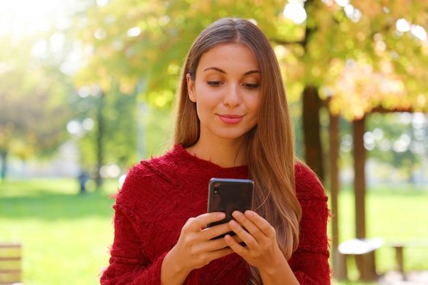 Schließen sie herauf des schönen mädchens, das das internetbrowsen auf smartphone auf herbst- oder wintersaison verwendet.