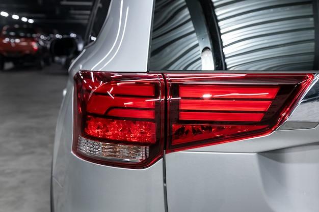 Schließen sie herauf detail über eines des modernen silbernen überkreuzungsautos des roten rücklichts led. außendetail automobil.