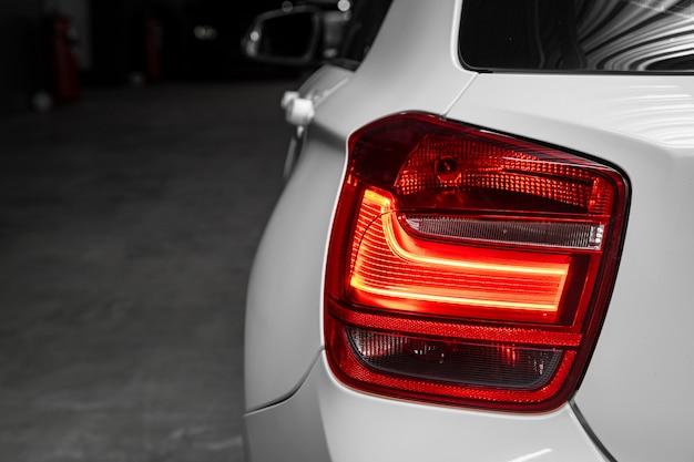 Schließen sie herauf detail über eines des modernen weißen limousinenautos des roten rücklichts led. außendetail automobil.