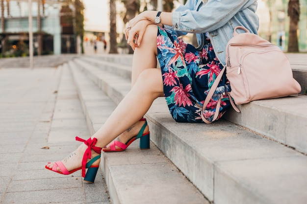 Schließen sie herauf details der beine in den rosa sandalen der frau, die auf treppen in der stadtstraße im stilvollen bedruckten rock mit lederrucksack, sommerarttrend sitzt