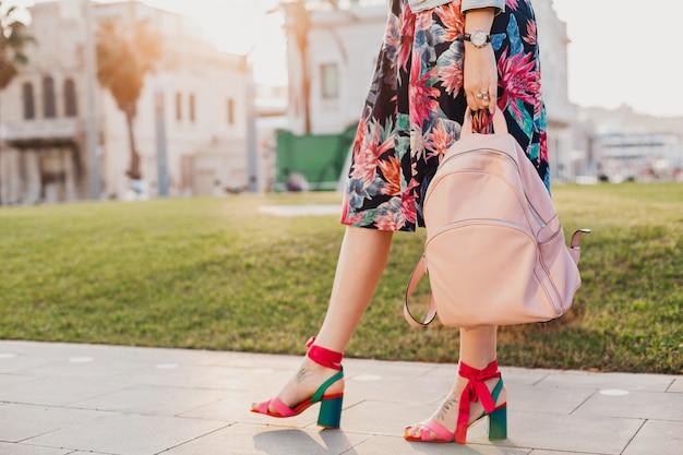 Schließen sie herauf details der beine in den rosa sandalen der stilvollen frau, die in der stadtstraße in bedrucktem buntem rock geht und rosa lederrucksack hält