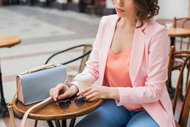 Schließen sie herauf details des zubehörs der stilvollen frau, die im café sitzt, das kaffee, sonnenbrille, handtasche, frühlingssommer-modetrend, eleganten stil trinkt