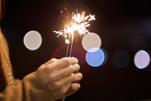 Schließen sie herauf die ansicht von den frauenhänden, die die wunderkerze halten und sylvesterabend feiern
