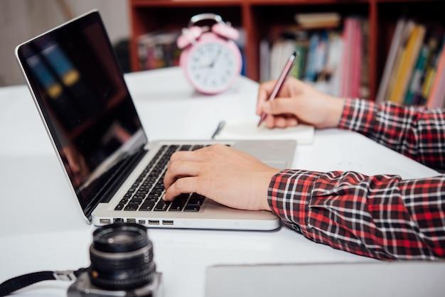 Schließen sie herauf die arbeit des jungen mannes und intelligentes telefon und laptop