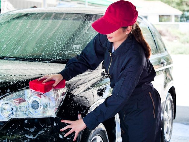 Schließen sie herauf die asiatische frau der arbeitskraft, die vor auto mit schaum an der garage wäscht.