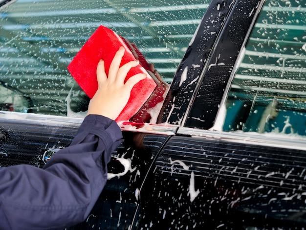 Schließen sie herauf die asiatische frauenhand der arbeitskräfte, die vor auto mit schaum an der garage sich wäscht.