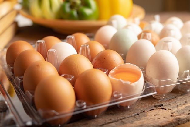Schließen sie herauf die eier des huhns und der ente, die auf einen holztisch gesetzt werden