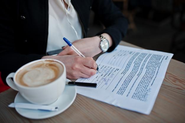 Schließen sie herauf die fotos des mädchens sitzend auf café mit tasse cappuccino und schreiben sie einige dokumente.