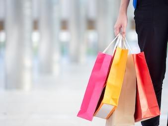 Schließen Sie herauf die Frau, die Einkaufstasche mit buntem Gehen in die Stadt mit copyspace hält