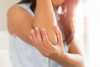 Schließen Sie herauf die Frau, die Schmerz in verletztem Ellbogen hat. Gesundheitswesen und Armschmerzkonzept.