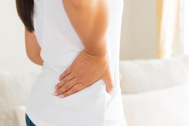 Schließen sie herauf die frau, die schmerz in verletzter rückseite hat. gesundheits-konzept.