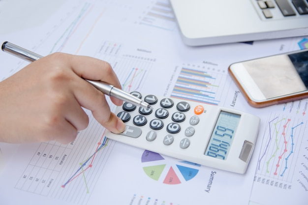Schließen sie herauf die frau, die taschenrechner auf papierdiagrammdaten mit dem handeln der finanzierung im büro verwendet.