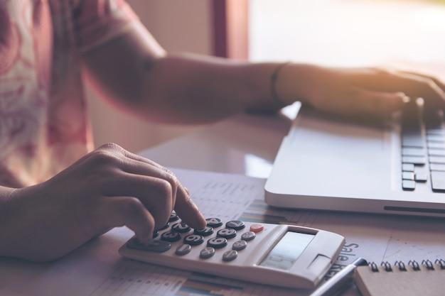 Schließen sie herauf die frau, die taschenrechner und laptop auf papierdiagrammdaten mit dem handeln von finanzierung im büro verwendet.