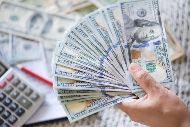 Schließen sie herauf die frauenhände, die bank von amerika-dollarbanknoten halten und zählen