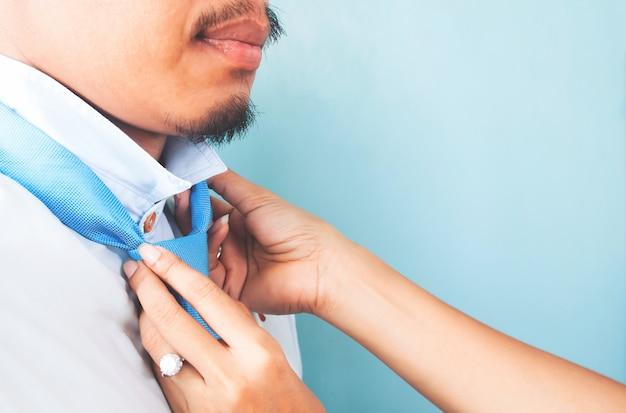 Schließen sie herauf die frauenhände, die krawatte des asiatischen kerls mit bart binden. liebe und familienkonzept