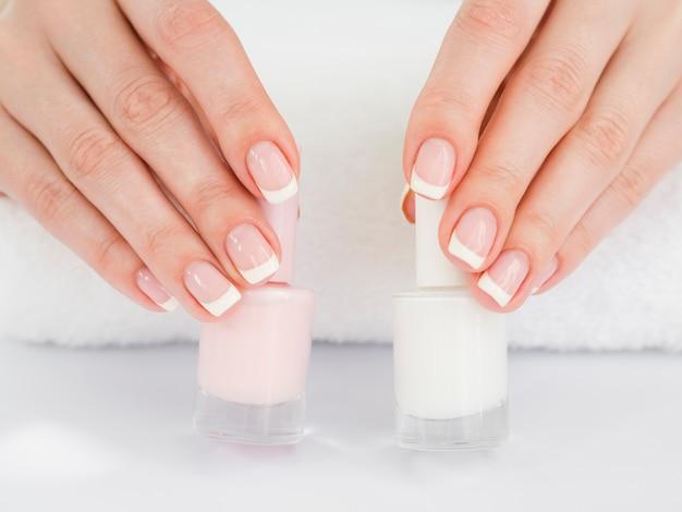 Schließen sie herauf die frauenhände, die nagellack halten