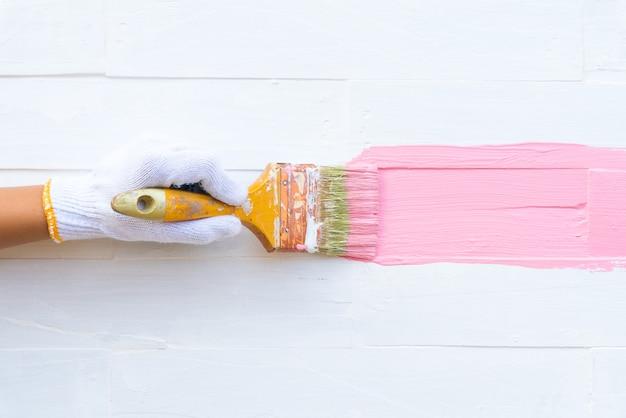 Schließen sie herauf die frauenhand, die bürste hält, die rosa farbe auf einem weißen holztisch malt