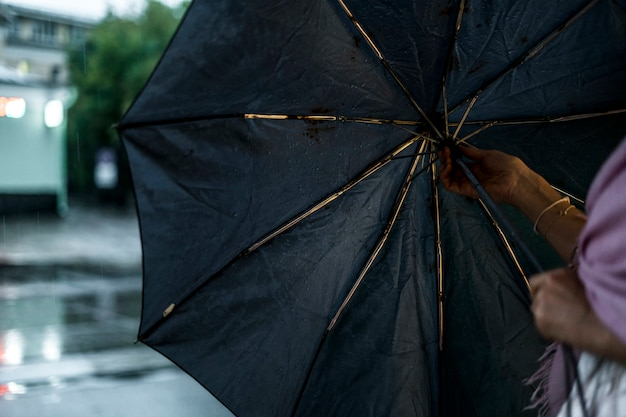 Schließen sie herauf die frauenhand, die den regenschirm während des regens in der stadt öffnet