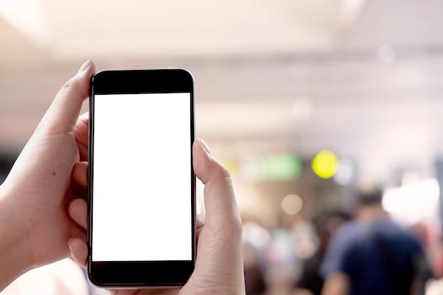 Schließen sie herauf die frauenhand, die ein intelligentes telefon mit leerem bildschirm am maket verwendet.