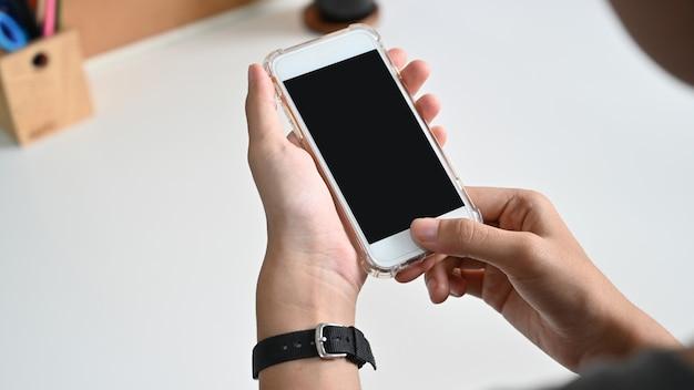 Schließen sie herauf die frauenhand, die ein intelligentes telefon mit leerem bildschirm am schreibtisch verwendet.