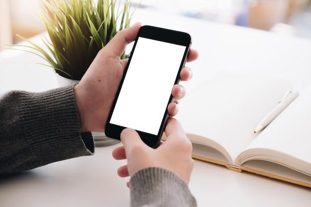 Schließen sie herauf die frauenhand, die zu hause ein intelligentes telefon mit leerem bildschirm verwendet.