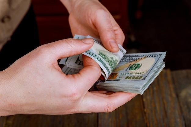 Schließen sie herauf die hände der frau us-dollar rechnungen zählend