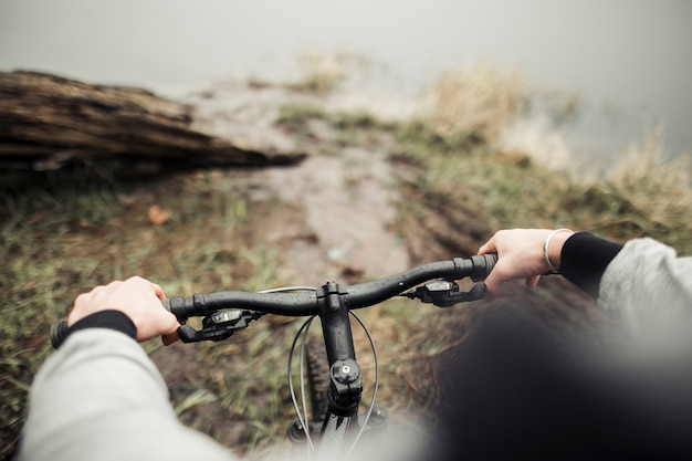Schließen sie herauf die hände des fahrradfahrers auf einer gebirgsfahrradlenkstange