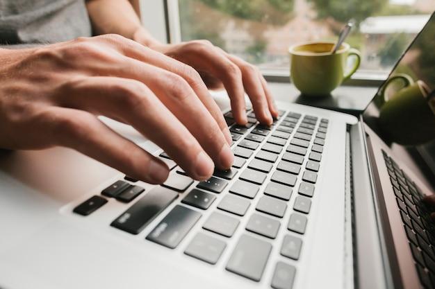 Schließen sie herauf die hände, die auf laptop schreiben