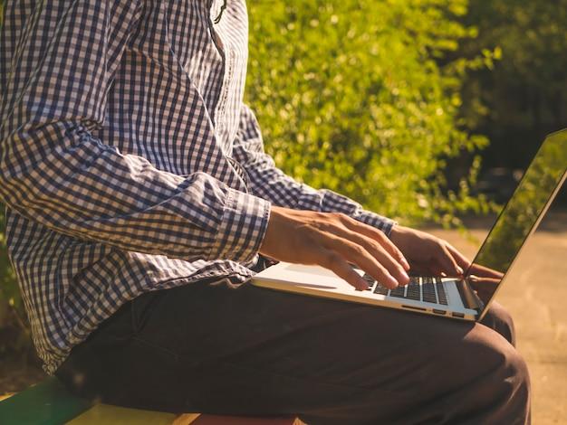 Schließen sie herauf die hände, die auf laptoptastatur draußen in der straße schreiben