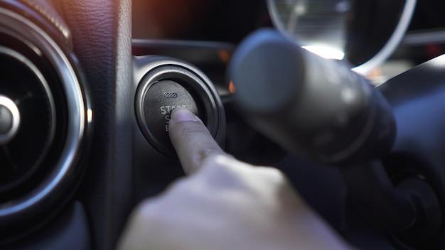 Schließen sie herauf die hand der frau, sie drückt startknopf im modernen auto.