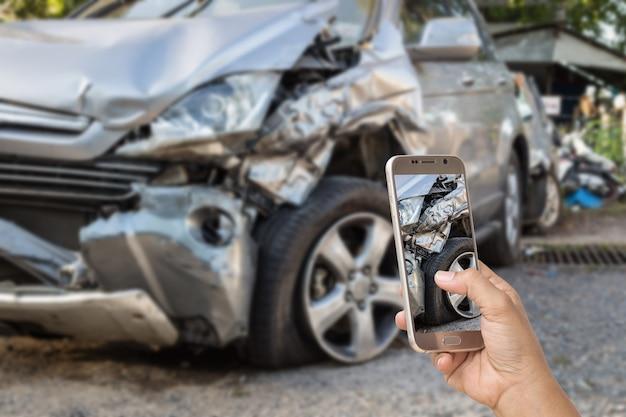 Schließen sie herauf die hand der frau smartphone halten und machen sie foto des autounfalls
