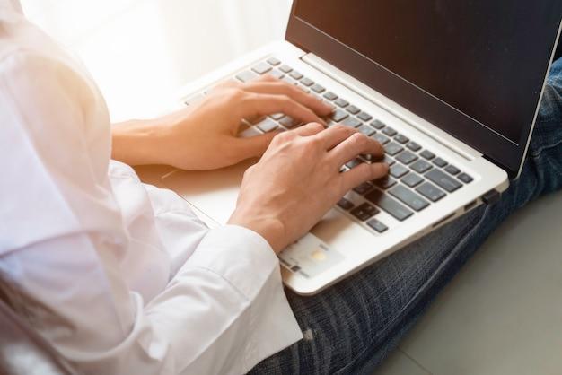 Schließen sie herauf die hand der geschäftsfrau schreibend auf der tastaturlaptop-computer und zu hause büro bearbeiten.